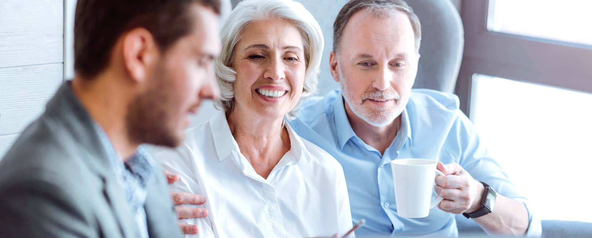 older couple smiling talking to an advisor